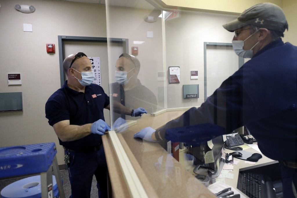In this Wednesday, May 20, 2020 photo carpenters John Mackie, of Canton, Mass., left, and Doug Hathaway, of Holliston, Mass., right, apply trim to a n...