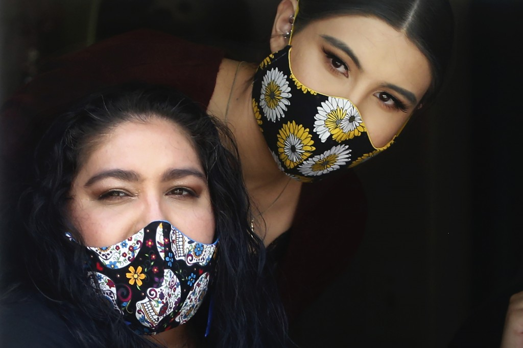 In this Monday, May 18, 2020, photo, Anissa Archuleta, right, and her mother, Jaime Ortega, sit at a window of their home in Midvale, Utah. Ortega and...