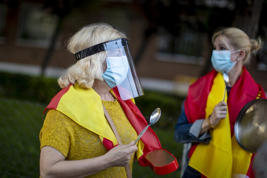 Women with Spanish flags on their shoulders bang saucepans during a protest against the Spanish government amid the lockdown to prevent the spread of ...