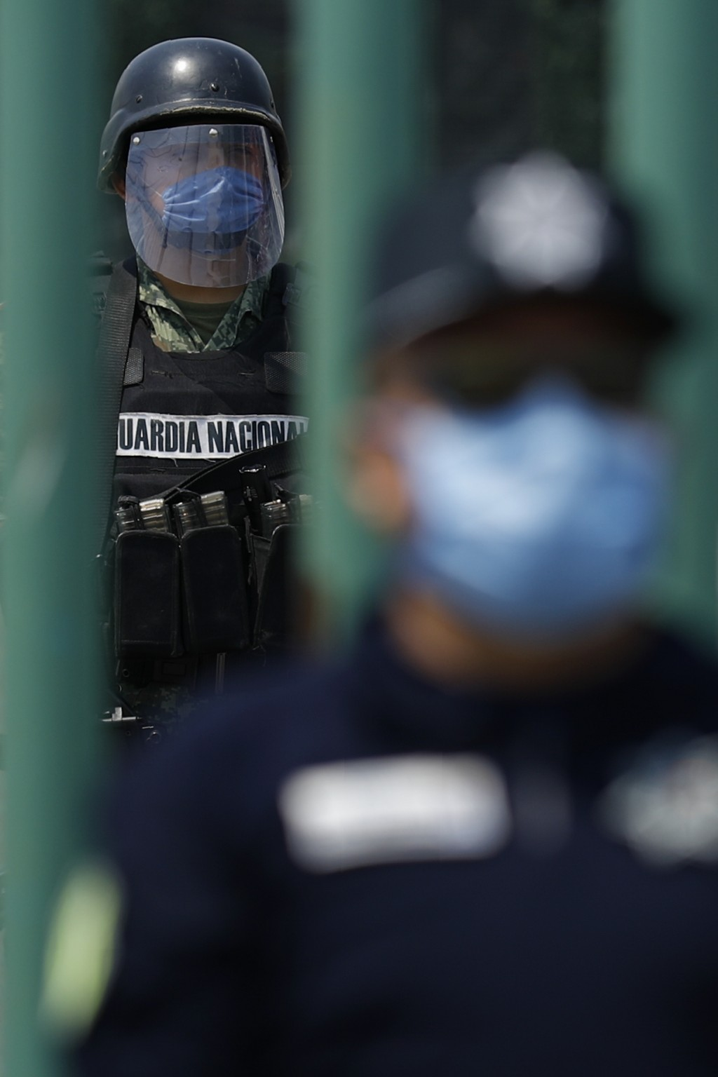 A member of the National Guard stands watch inside the gates as state police guard the street outside, at Las Americas General Hospital in Ecatepec, a...