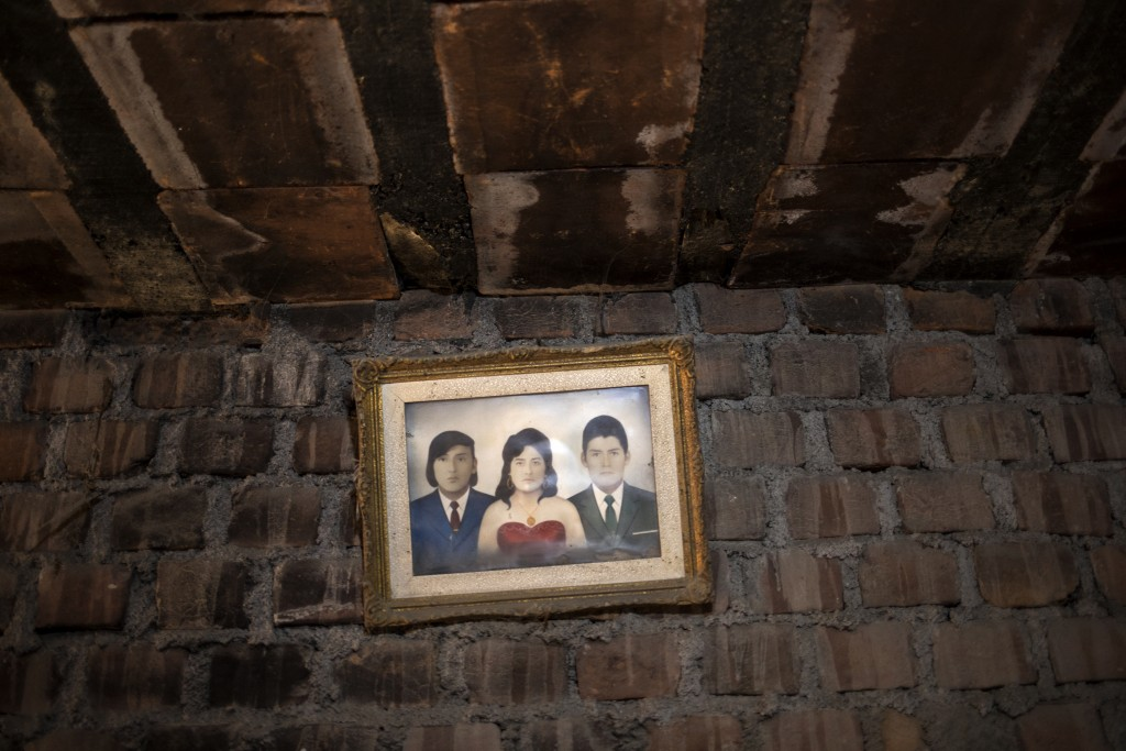 A family portrait hangs on a wall in the home of a person who is suspected to have died from the new coronavirus, in Lima, Peru, Thursday, May 14, 202...
