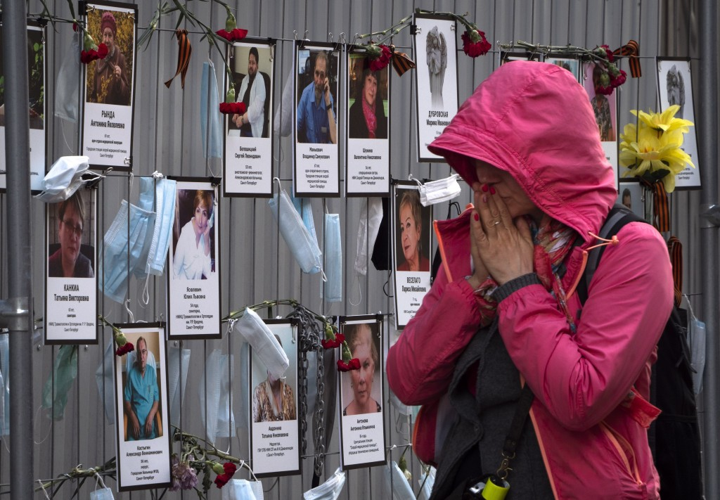In this Wednesday, May 20, 2020 photo, a woman reacts as she walks past portraits of St. Petersburg's medical workers who died from coronavirus infect...