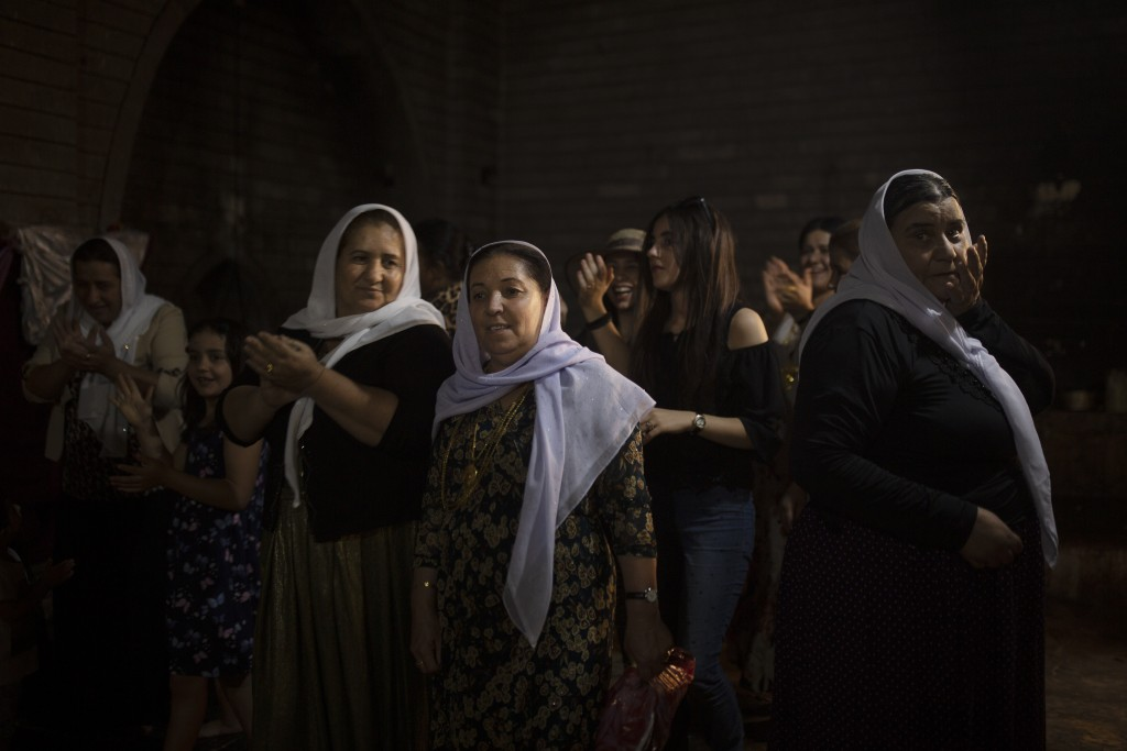 In this Sept. 12, 2019 photo, Yazidi women visit Lalish, the holiest Yazidi shrine, in Iraq's Dohuk province, in northern Iraq. During a week-long ass...
