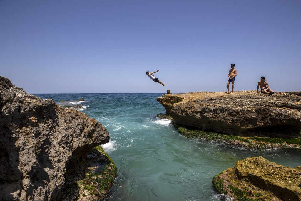 A Lebanese youth jumps into the Mediterranean Sea off the corniche, in Beirut, Lebanon, Monday, May 18, 2020. Lebanon partially reopened its economy M...