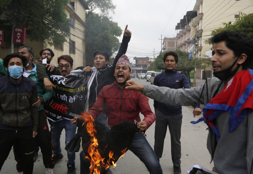 FILE - In this  Monday, May 11, 2020, file photo, Nepalese students shout slogans during a protest against the Indian government inaugurating a new ro...