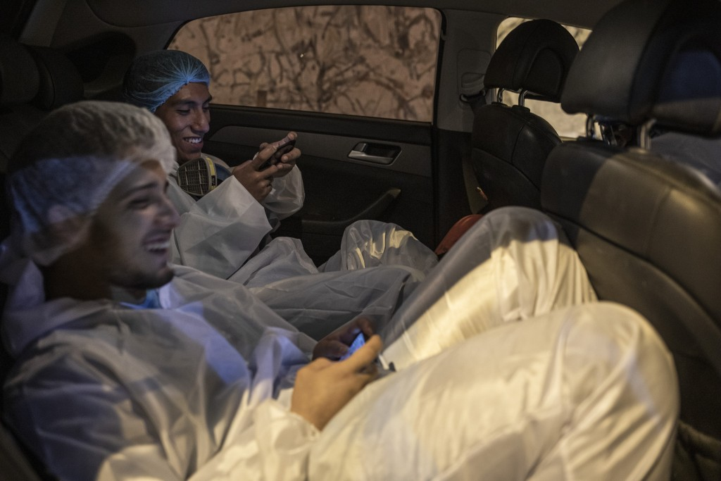 Piedrangel funeral home workers, Venezuelan Luis Zerpa and Peruvian Angelo Aza, pass the time playing games on their smartphones as they wait for the ...