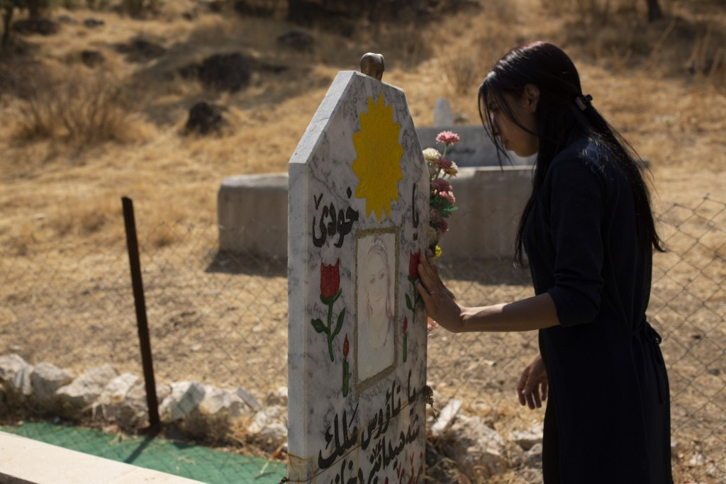 In this Sept. 13, 2019 photo, Layla Taloo visits the grave of a Yazidi woman who took her own life after she was captured by Islamic State militants i...