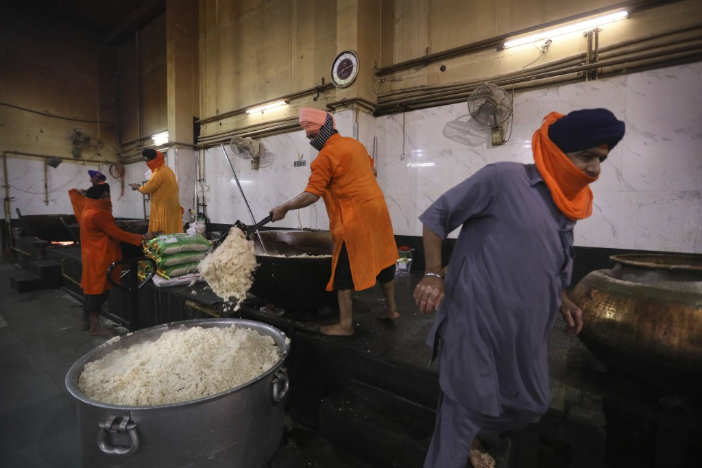 A Sikh volunteer scoops out cooked rice into a large vessel in the kitchen hall of the Bangla Sahib Gurdwara in New Delhi, India, Sunday, May 10, 2020...
