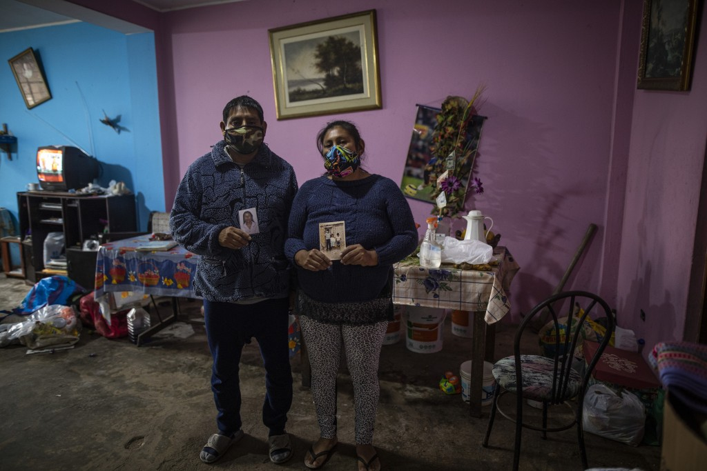 Siblings Jorge and Julia Lopez pose for a photo holding family snapshots in the living room where their father Faustino Lopez committed suicide days a...