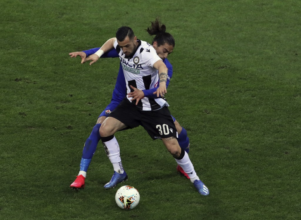 FILE - In this March 8, 2020 file photo, Fiorentina's Martin Caceres and Udinese's Ilija Nestrovski, foreground, vie for the ball during the Italian S...