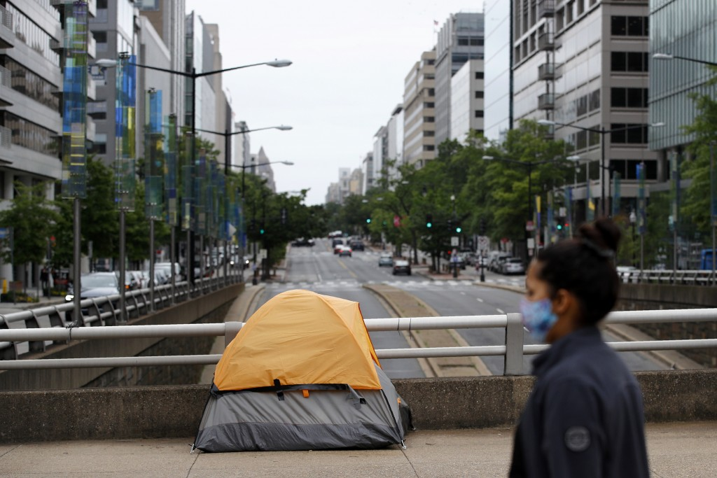 A homeless person's tent sits above a quiet K Street Northwest as a woman wearing a face mask to protect against the spread of the new coronavirus wal...