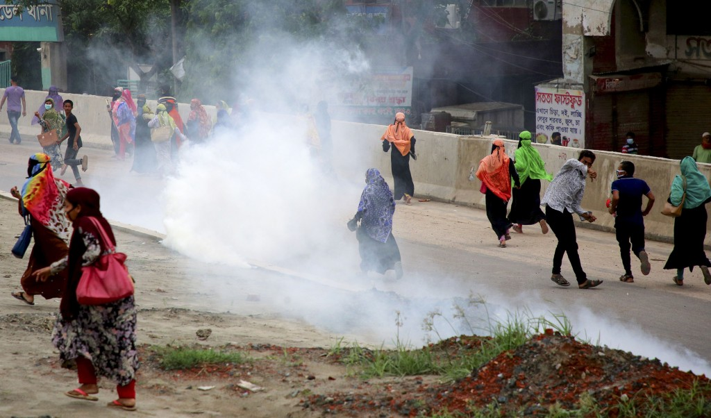 Bangladeshi garment workers run for cover after police fired tear gas to disperse them during a protest in Dhaka, Bangladesh, Wednesday, May 20, 2020....