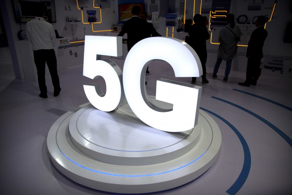 FILE- In this Sept. 26, 2018, file photo visitors stand near a 5G logo at a display the PT Expo in Beijing. AT&T says it will stop advertising its wir...
