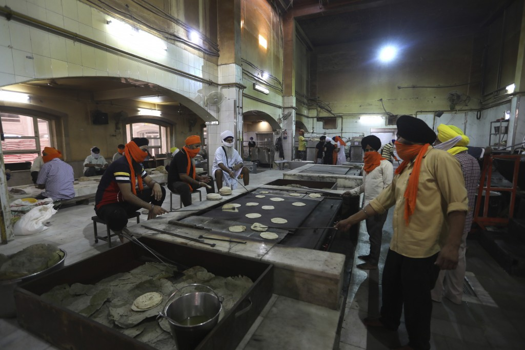 Sikh volunteers make chapatis, thin unleavened breads, in the kitchen hall of the Bangla Sahib Gurdwara in New Delhi, India, Sunday, May 10, 2020. The...