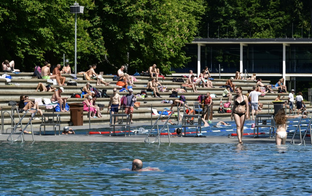 People enjoy the warm sunny weather during the opening day of the public open air pool in Cologne, Germany, Thursday, May 21, 2020. Public swimming po...