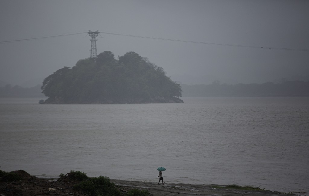 An Indian fisherman walks in the middle of heavy wind and rain along the river Brahmaputra in Gauhati, India, Thursday, May 21, 2020. A powerful cyclo...