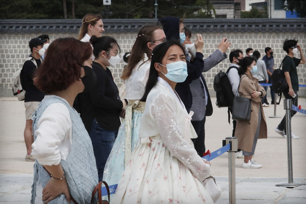 Visitors waring face masks watch a reenactment of the Royal Guards Changing Ceremony, which had been suspended due to the new coronavirus, at Gyeongbo...
