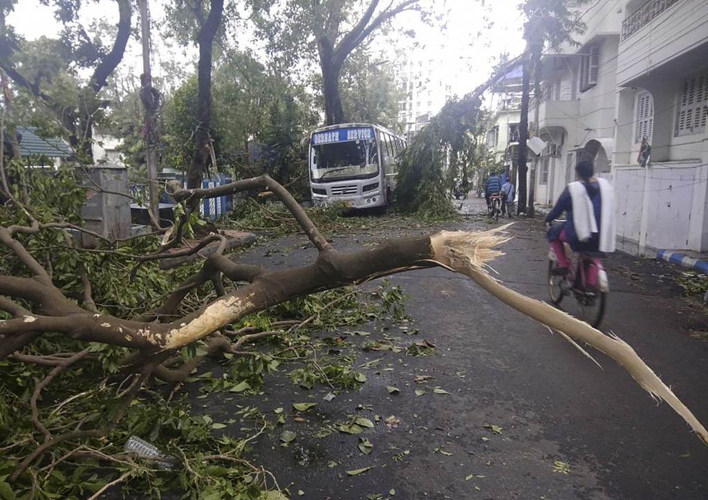 A girl rides a cycle past tree branches that fell after cyclone Amphan hit the region, in Kolkata, India, Thursday, May 21, 2020. A powerful cyclone t...