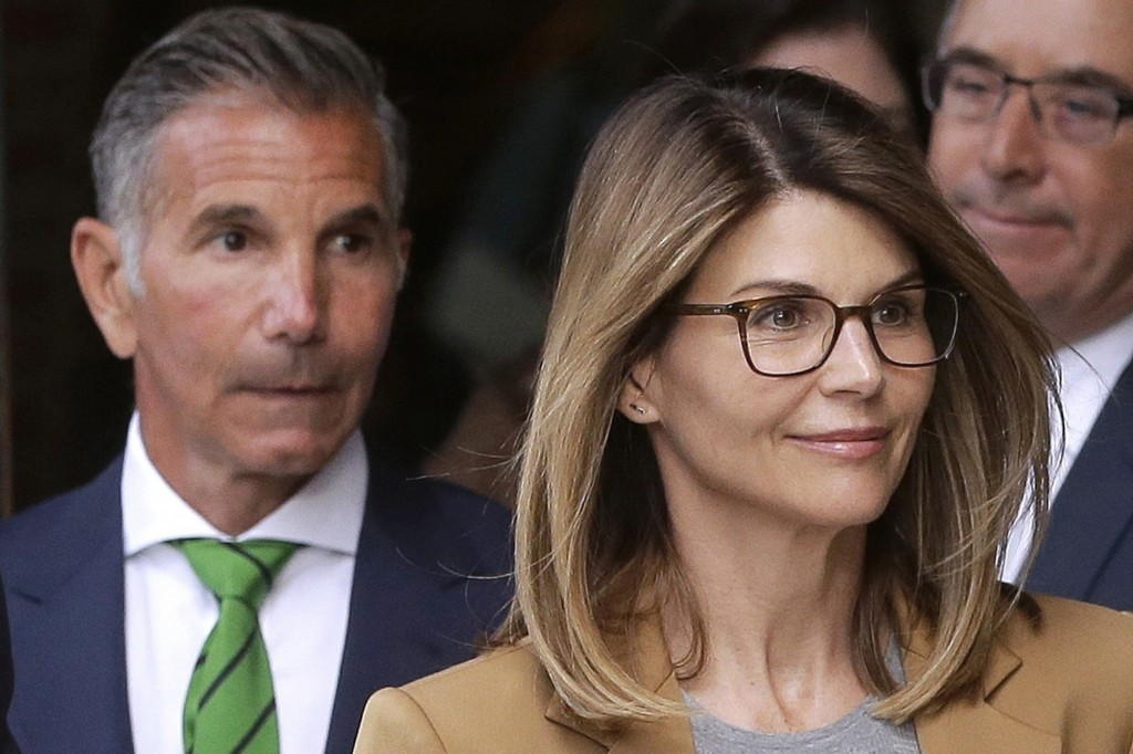 FILE - In this April 3, 2019, file photo, actress Lori Loughlin, front, and her husband, clothing designer Mossimo Giannulli, left, depart federal cou...