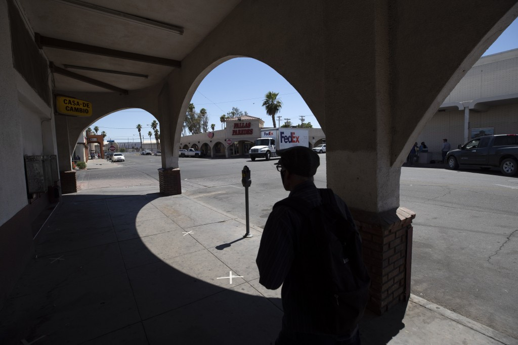 A man walks by nearly empty streets Wednesday, May 20, 2020, in Calexico, Calif. As much of California inches toward businesses reopening, this farmin...