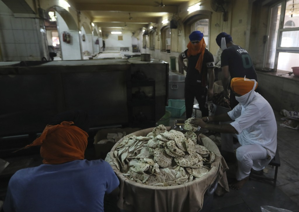 Sikh volunteers take out cooked chapatis, thin unleavened breads, from a machine in the kitchen hall of the Bangla Sahib Gurdwara in New Delhi, India,...