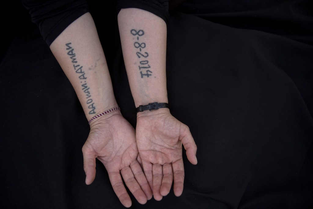 In this Thursday, Aug. 29, 2019 photo, Leila Shamo displays tattoos she made while enslaved by Islamic State militants at her home near Khanke Camp, n...