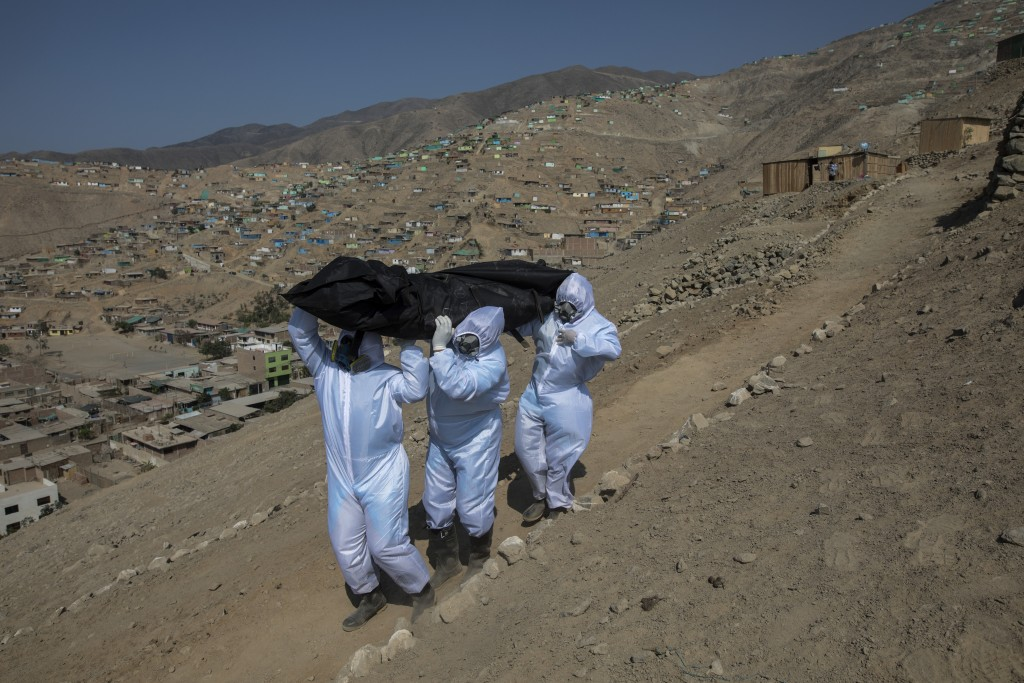 Venezuelans Luis Zerpa, from left, Luis Brito and Jhoan Faneite, carry a body bag that contains the remains of 51-year-old Marcos Espinoza who is susp...