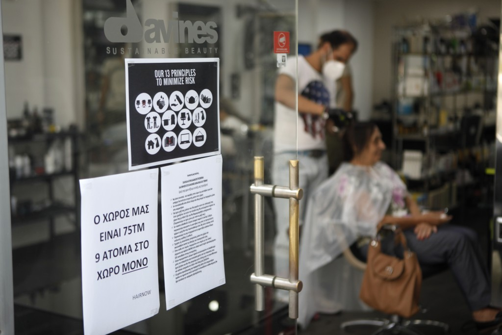 Protection informations for the clients at the entrance of a hair salon as a hairdresser wearing a mask to protect against coronavirus attends to clie...
