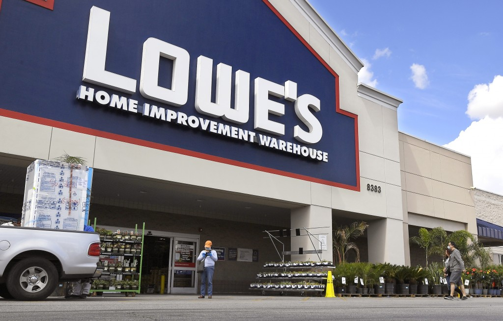 FILE - In this March 22, 2020 file photo, customers wearing masks walk into a Lowe's home improvement store in the Canoga Park section of Los Angeles....
