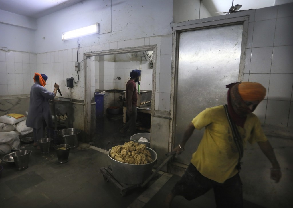 A Sikh volunteer carries dough for making chapati, thin unleavened bread, as others prepare spices in the kitchen hall of the Bangla Sahib Gurdwara in...