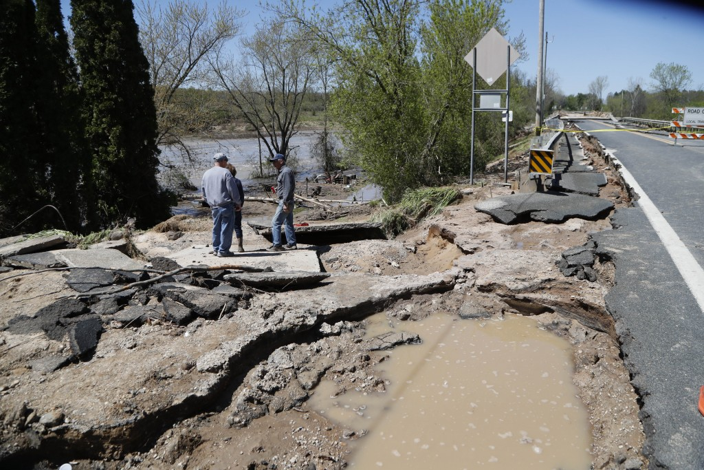 Bob Yahrmarkt, right, stands on his washed out driveway next to his home, Wednesday, May 20, 2020, in Edenville, Mich. Some people living along two mi...