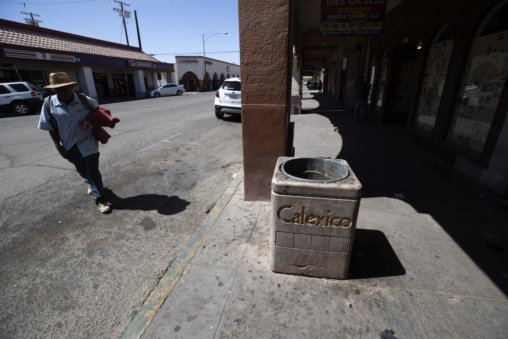 A man walks down a nearly empty street, Wednesday, May 20, 2020, in Calexico, Calif. As much of California inches toward businesses reopening, this fa...