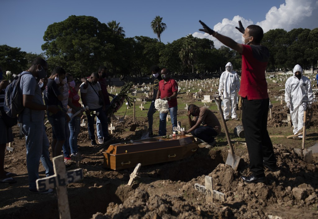Relatives pray during the burial of Amanda da Silva, who died of COVID-19 at the Caju Cemetery, in Rio de Janeiro, Brazil, Wednesday, May 20, 2020. (A...
