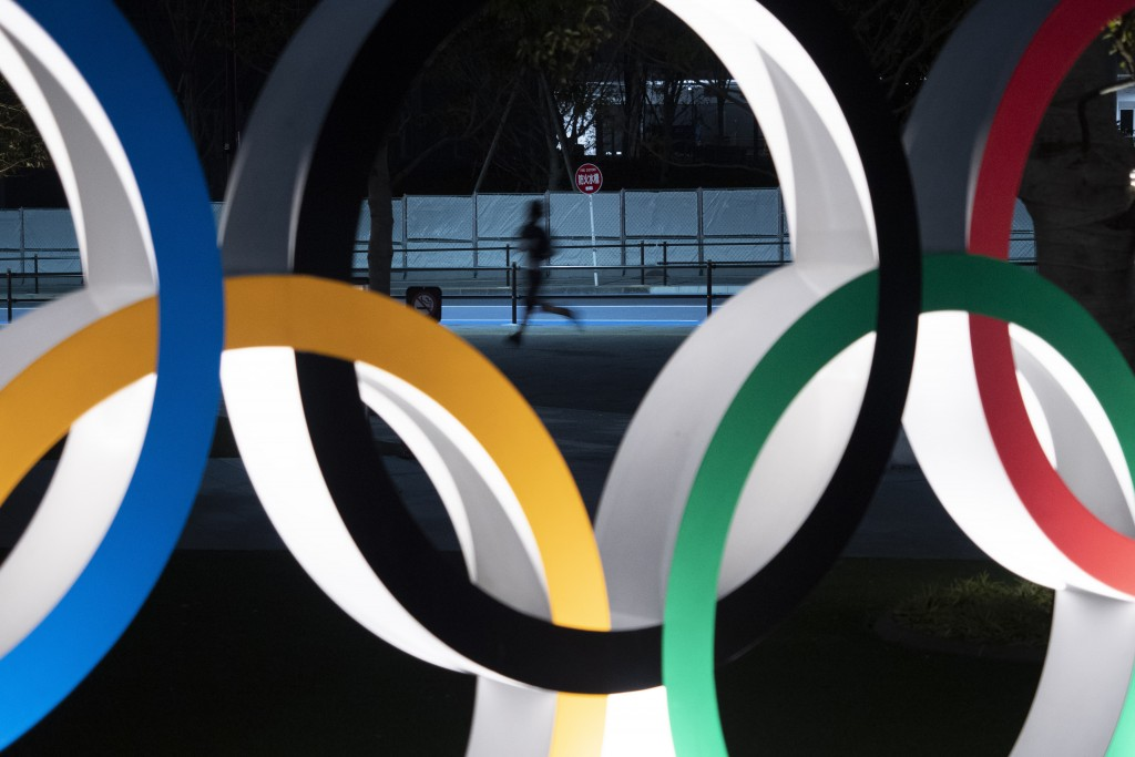 FILE - In this March 30, 2020, file photo, a man jogs past the Olympic rings in Tokyo. Tokyo Olympic CEO Toshiro Muto talked Thursday, May 21, about t...