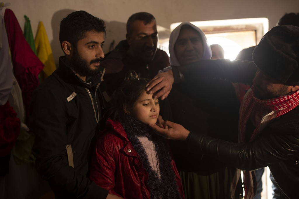 In this Feb. 12, 2020 photo, Malak Saad Dakhel, 11, is anointed by a holy man inside a Yazidi shrine as she is welcomed home by her relatives after he...