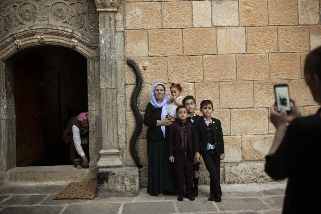 In this Aug. 23, 2019 photo, a Yazidi family poses for a photo at the door to the Lalish temple near Sheikhan, Iraq. The ancient sect is rebuilding, n...