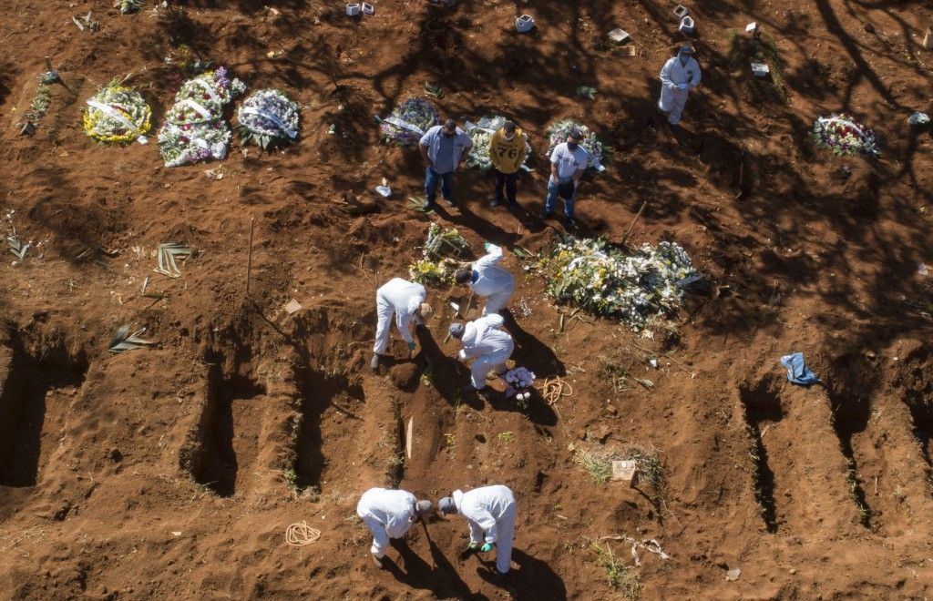 Cemetery workers in protective clothing bury a COVID-19 victim at the Vila Formosa cemetery in Sao Paulo, Brazil, Wednesday, May 20, 2020. (AP Photo/A...