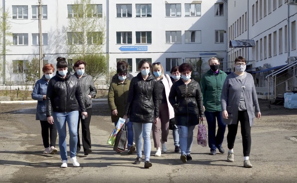 In this photo taken from video footage, nurses and orderlies walk to meet journalists in front of a hospital in Russia's Siberian city Chita, Russia, ...