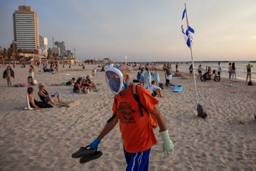 A man wears a diving mask uses as a protective face mask at the beach front in Tel Aviv, Israel, Saturday, May 16, 2020. Israeli authorities have rece...