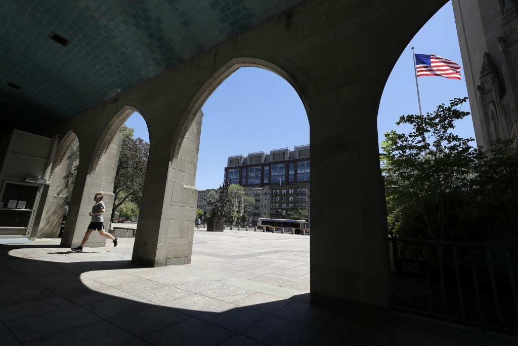 In this Wednesday, May 20, 2020 photo a runner passes through an arch on the campus of Boston University, in Boston. Boston University is among a grow...