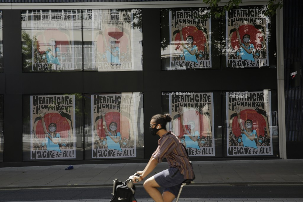 A man wearing a face mask cycles past a coronavirus related artwork displayed on screens in the window of the Flannels clothing store on Oxford Street...