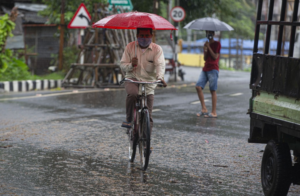 An Indian man rides on a bicycle in the middle of heavy wind and rain in Gauhati, India, Thursday, May 21, 2020. A powerful cyclone ripped through den...