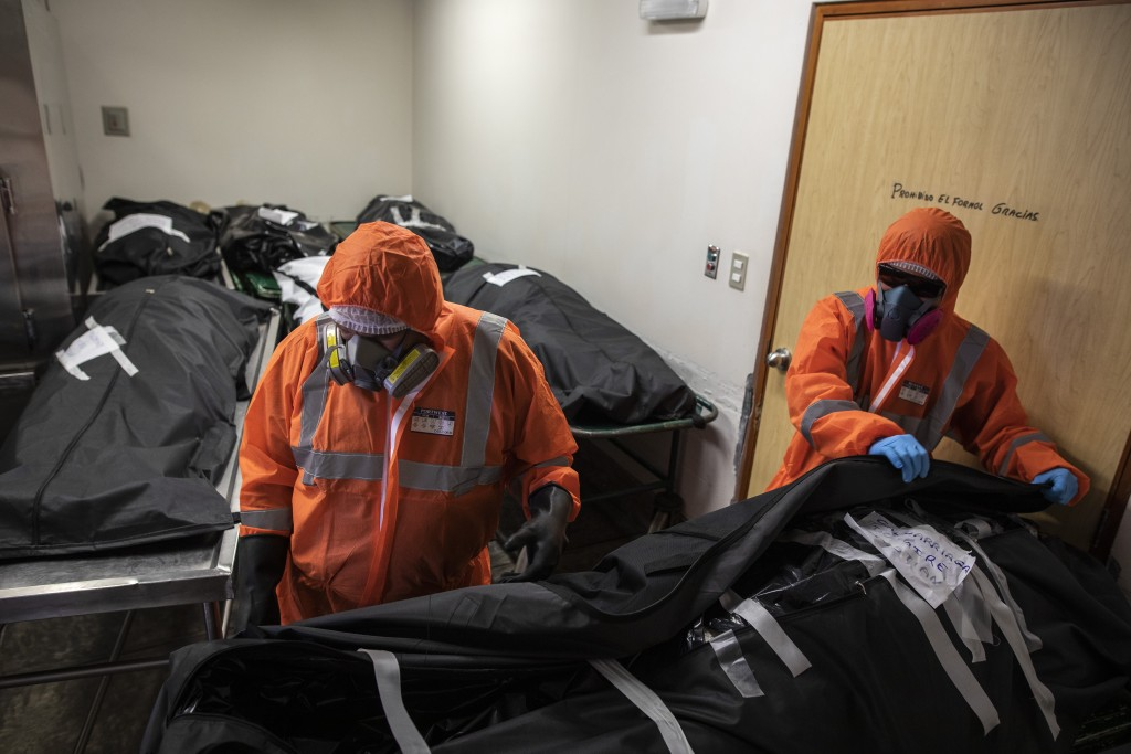 Piedrangel funeral home workers, Luis Zerpa of Venezuela and Peruvian Angelo Aza, prepare to remove bodies of deceased persons who are suspected to ha...