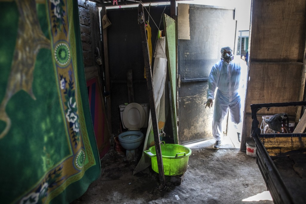 Piedrangel funeral worker Alexander Carballo, of Venezuela, enters a home to remove the body of a person who is suspected to have died from the new co...