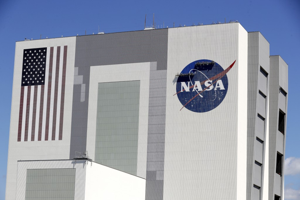 Workers near the top of the 526 ft. Vehicle Assembly Building at the Kennedy Space Center spruce up the NASA logo standing on scaffolds in Cape Canave...