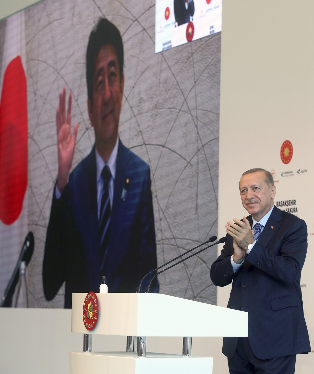 In this photo provided by the Turkish Presidency, Turkey's President Recep Tayyip Erdogan applauds Japanese Prime Minister Shinzo Abe via video link, ...