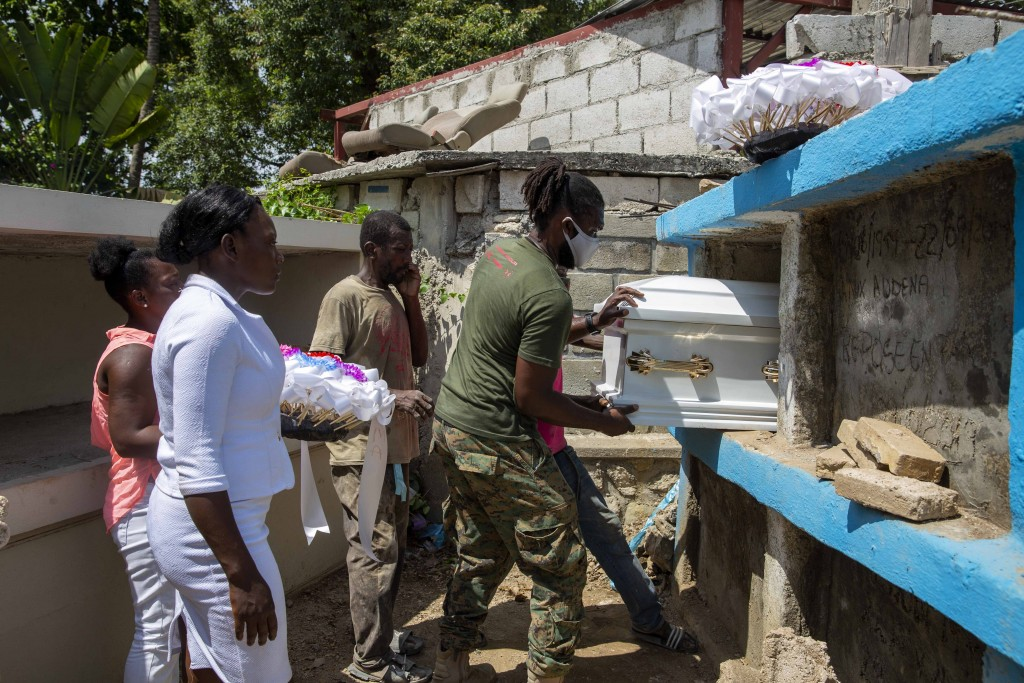 Cemetery workers push the coffin with the body of 7-year-old Lovena Luberice into its niche at the Freres Public Cemetery in Port-au-Prince, Haiti, We...