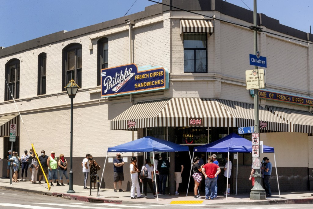 FILE - In this Saturday, May 2, 2020 file photo people stand in line while following social distancing guidelines as they wait for French dip sandwich...