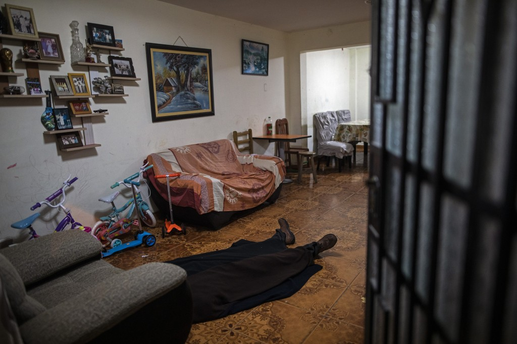 The body of Ricardo Noriega, suspected of dying from the new coronavirus, lies covered by a blanket on his living room floor in Lima, Peru, Monday, Ma...