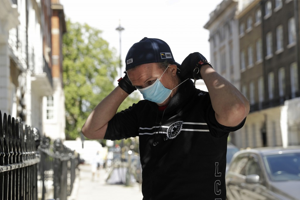 In this May 18, 2020, photo, medical courier Ben Gee, who works for The Doctors Laboratory, puts on a surgical face mask before entering a medical off...